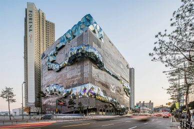 oma shapes gwanggyo galleria department store as a sculpted stone textured with mosaic stone and multifaceted glass facade